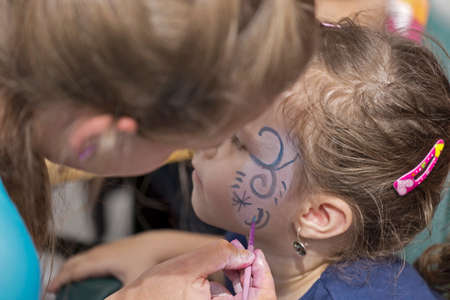 children painting: TIMISOARA, ROMANIA - JUNE 01, 2016: Workshop with face painting for children,  in a park in Timisoara, Romania. International children Day. Editorial