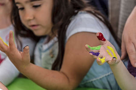 kids painted hands: TIMISOARA, ROMANIA - JUNE 01, 2016: Kids painted hands.  Workshop organized by the City Hall Timisoara with the occasion of the International children Day. Happy childhood.