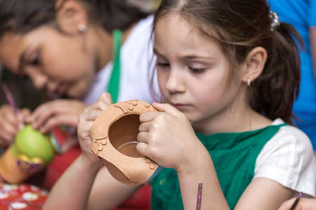 TIMISOARA, ROMANIA - JUNE 1, 2016: Girls who paints a ceramic bowl. Workshop organized by the City Hall Timisoara with the occasion of the International children Day.