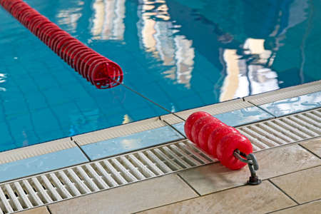 Background with a swimming pool and red markers between lanes competition. Stock Photo