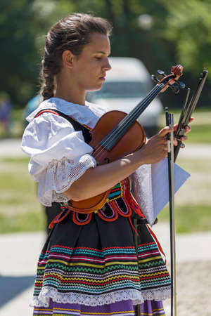 ROMANIA, TIMISOARA-JULY 10, 2016:Singer at violin from Poland in traditional costume, present at the international folk festival International Festival of hearts organized by the City Hall Timisoara
