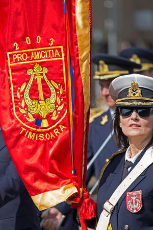 organized unit: TIMISOARA, ROMANIA - SEPTEMBER 25, 2016: Military parade with unit flag worn by a woman. Show organized by the Municipality of Timisoara.