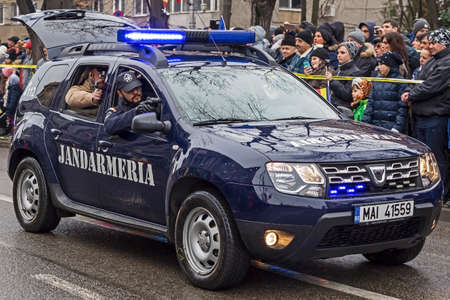 subversion: TIMISOARA, ROMANIA - DECEMBER 1, 2016: Military parade at Romanian National Day. Cops from gendarmerie simulating a mission. Picture taken in front of the Administrative Palace in Timisoara.