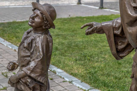 ALBA IULIA, ROMANIA - APRIL 29, 2017: Group of bronze statues in Alba Carolina Citadel, Fortress square, depicting an old priest and child on the street, symbolizing medieval time.