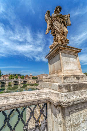 ROME, ITALY - JUNE 1, 2017: Statue of Agnel from Angels Bridge by sculptor Ercole Ferrata, in front of castle San Angelo. Vatican Basilica in background. Editorial