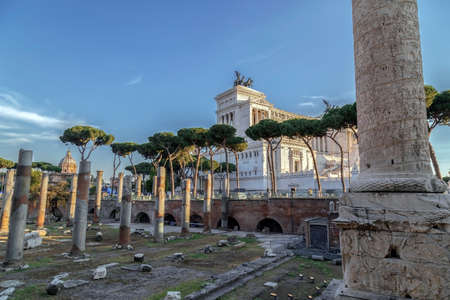 architecture monumental: Ruins of Trajan forum with Trajan column and Vittorio Emmanuele II monument in background. Rome, Italy.