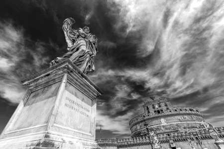 ROME, ITALY - JUNE 1, 2017: Black and white photo with statue of Angel from Angels Bridge by sculptor Ercole Ferrata, in front of castle San Angelo. Vintage processing.