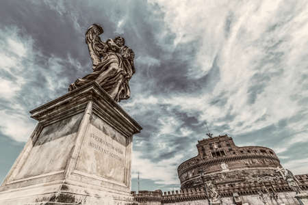 ROME, ITALY - JUNE 1, 2017: Old photo with statue of Angel from Angels Bridge by sculptor Ercole Ferrata, in front of castle San Angelo. Vintage processing. Editorial