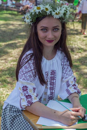 TIMISOARA, ROMANIA - JUNE 24, 2017: Young girl dressed in traditional Romanian blouse called IE, with flower head crown. A show organized by the City Hall on the occasion of the IEI national day.