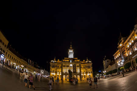 street lamp: NOVI SAD, SERBIA - JULY 30, 2017: Night view of the Liberty Square (Trg. Slobode) with City Hall, tourists and old buildings. One of the cities designated as the European capital of culture in 2021.