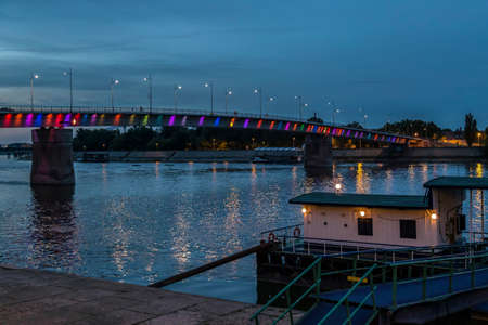 Night view of the Rainbow Bridge on the Danube River in Novi Sad, Serbia with a pontoon of boats in front. Reklamní fotografie