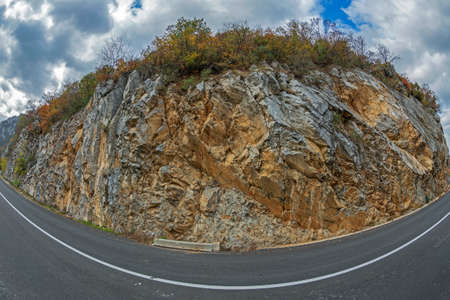 Rock wall background with autumn vegetation along a road.