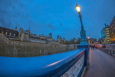 LONDON, ENGLAND - NOVEMBER 27, 2017: View along the street at dusk time of the Royal Palace Fortress, Tower of London, historic castle on the north bank of the River Thames in central London.