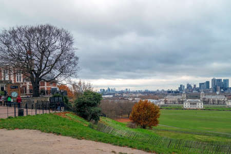 LONDON,ENGLAND - NOVEMBER 29, 2017: Panoramic view with people that visit Royal Greenwich Observatory at Greenwich Hill, skyline of Canary Wharf and Queens House.