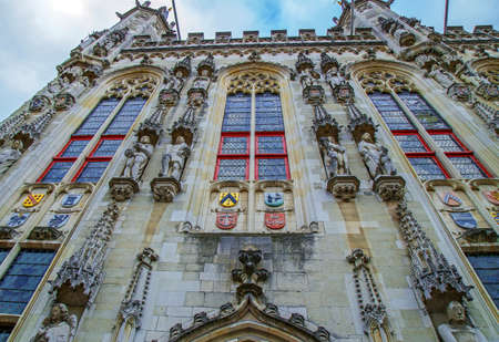 BRUGES - BELGIUM, OCTOBER 13, 2015: Architectural facade detail at City Hall, one old building placed in Burg square, Bruges, Belgium