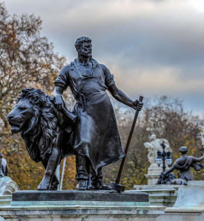 LONDON, UK - NOVEMBER 29, 2017: One of four bronze statues around the Queen Victoria Memorial in front of the Buckingham Palace.The monument was unveiled in 1911, with one fountain and bronze figures.