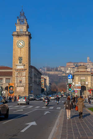 BERGAMO, ITALY - DECEMBER 12, 2016: Street and traffic in center of city with Bell tower in front and Citta Alta on background. People on the street.