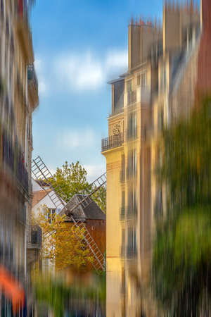 View along the street with old restaurant with windmill Moulin de la Galette situated in the district of Montmartre in Paris. Motion blur filter applied. Zdjęcie Seryjne