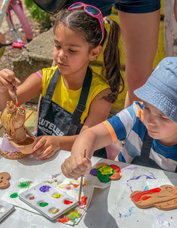 TIMISOARA; ROMANIA - JUNE 1; 2018: Children that paints ceramic funny objects. Workshop organized by the City Hall Timisoara with the occasion of the International children Day.