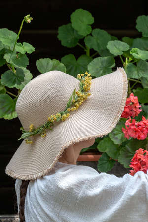 Woman with straw hat on a flower background. Stock Photo