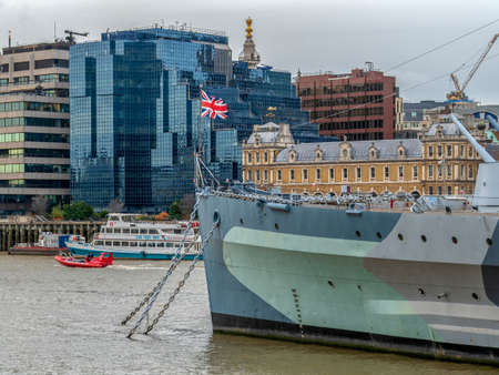 LONDON, UK - NOVEMBER 27, 2017: View with the historic HMS Belfast battleship and skyscrapers from Canary Wharf, on the Bank of River Thames.