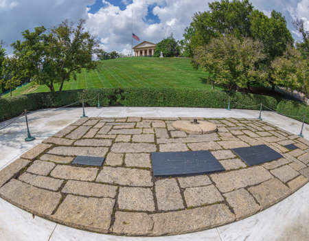ARLINGTON, VIRGINIA, USA - AUGUST 31, 2018: J. F. Kennedy and Jacqueline Onassis graves with eternal flame and mansion in the background at Arlington National Cemetery. Editorial