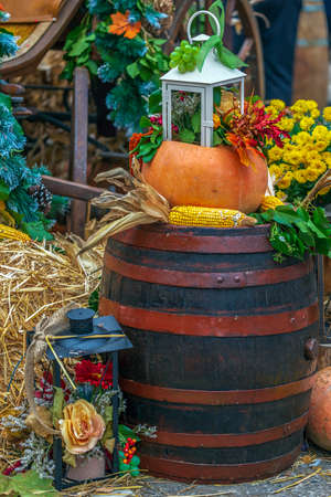 Autumn arrangement with pumpkins, corn, barrel and lamps.