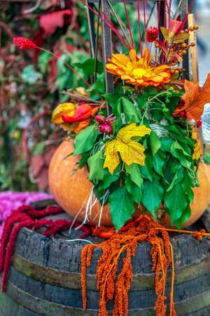 Autumn arrangement with pumpkins, barrel and flowers.