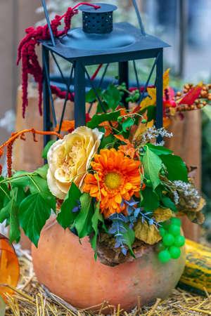Autumn arrangement with pumpkins, flowers and lamp.