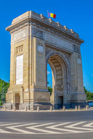 Bucharest, Romania - July 17, 2018: Triumphal Arch with flag, landmark architecture in the northern part of Bucharest, on the Kiseleff Road.