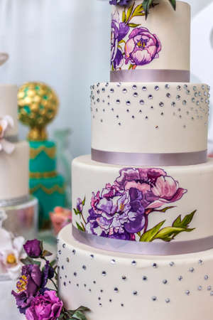 Wedding cake decorated with artificial flowers and painted.
