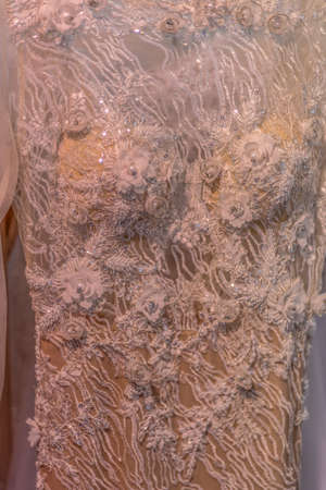Detail of a wedding dress decorated with crystals and lace.