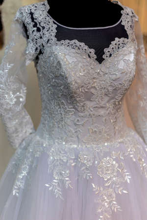 Detail of a wedding dress decorated with crystals, lace and veils.
