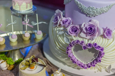 Wedding cake and specific sweets decorated with artificial flowers and painted.