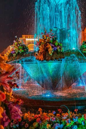 Multi colored illuminated fountain on the Plaza Opera in Timisoara, Romania, at night.