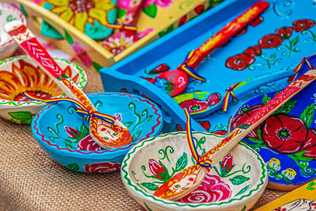 Spoons, bowls and wooden trays carved and painted with traditional Romanian patterns and used as decorative objects. Фото со стока