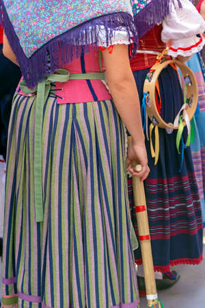 Detail of Italian folk costume for woman with multi colored embroidery and one musical instrument.
