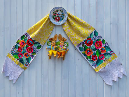 Decorative Easter figurines and romanian embroidery placed on a wooden wall. Фото со стока