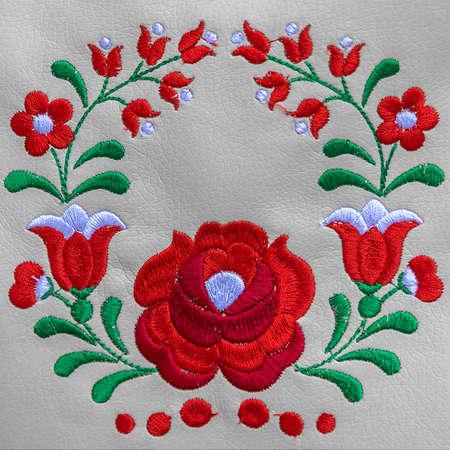 Arrière-plan avec des détails de broderie folklorique traditionnelle hongroise faite à la main sur un support en cuir.