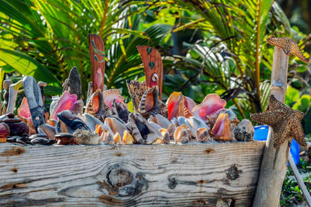 Specifical trinkets and colorful handicraft items made from shells, bamboo and palm trees, offered for sale to tourists on a beach with palm trees in Punta Cana, Dominican Republic.