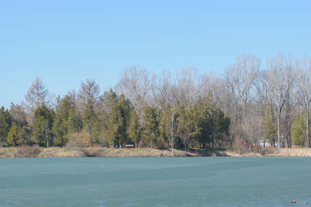 Frozen lake in spring time at Memorial Park Constantin Stere in Bucov, near Ploiesti, Romania