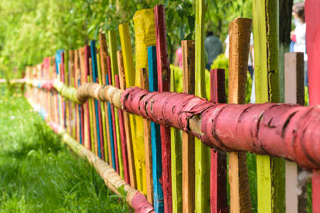 colorful red yellow blue green painted wood fence Stock Photo