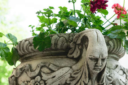 antique vase: Ancient flower pot holder made from brute stone - very old sculpture with scarry face - gothic style Stock Photo