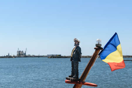 A sailor toy and the blue, yellow and red romanian flag mounted on a ships mast. The Black Sea in the background