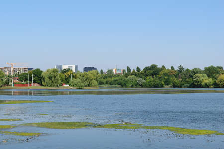 lake district: Plumbuita lake in Colentina district of Bucharest. Calm lake with vegetation, office buildings, flats and cranes in the background.