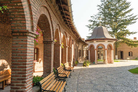 brick arcades, wood benches in exterior court of Plumbuita Monastery, Bucharest, Romania   Stock Photo