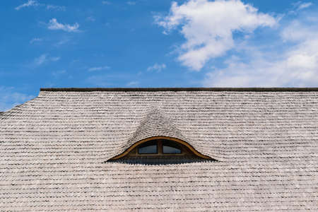 old traditional wood planks tiles roof with eye like window 스톡 콘텐츠