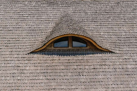 old traditional wood planks tiles roof with eye like window closeup
