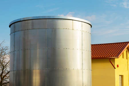 large metal tank container installed next to a house