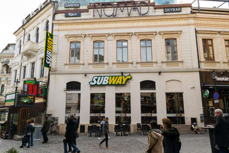Bucharest, Romania - March 16, 2019: Tourists walking by Subway restaurant on Lipscani street in Old Town part of Bucharest, Romania.